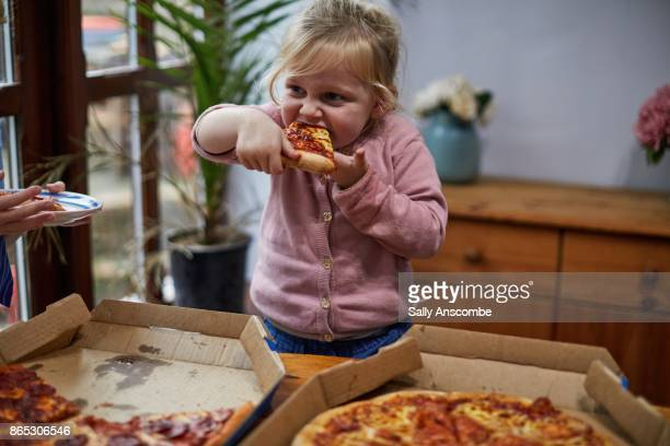 child eating a slice of pizza - take away food stock pictures, royalty-free photos & images