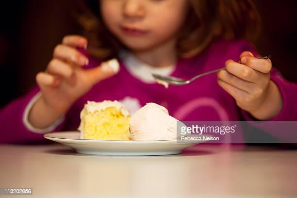 Child eating birthday cake and ice cream