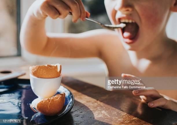 child eating egg - abbracciarsi a letto foto e immagini stock