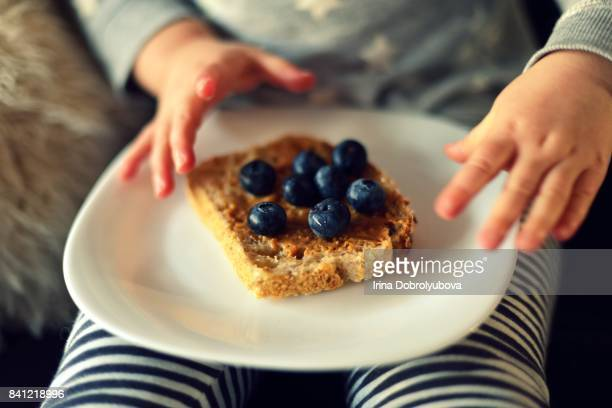 child eating sourdough toast with blueberries