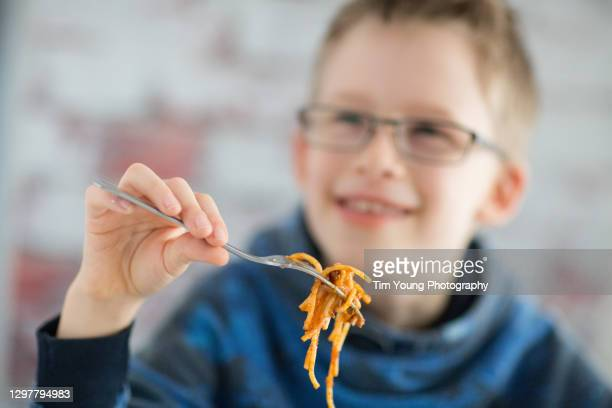 child eating spaghetti bolognese - primary age child stock pictures, royalty-free photos & images