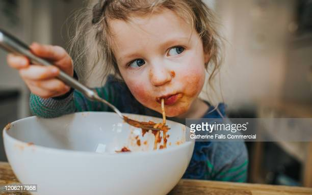 child eating spaghetti - british people stock pictures, royalty-free photos & images