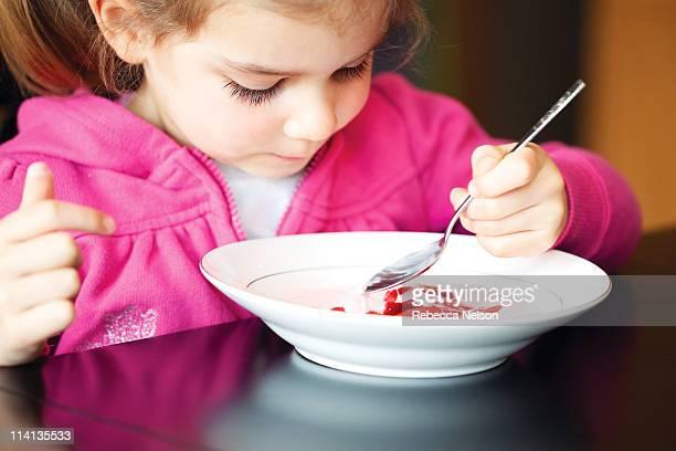 Child eating stawberries and yogurt