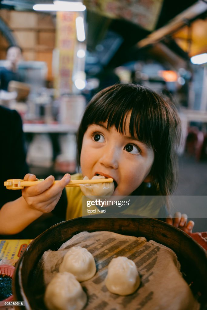 Child eating xiaolongbao at night market, Taiwan : Stock Photo