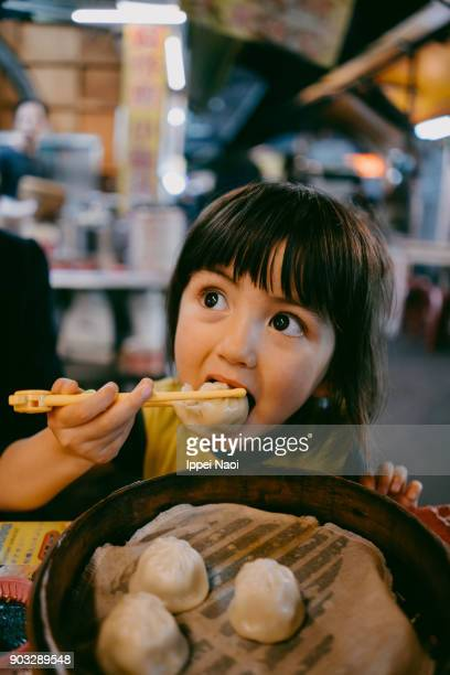 Child eating xiaolongbao at night market, Taiwan