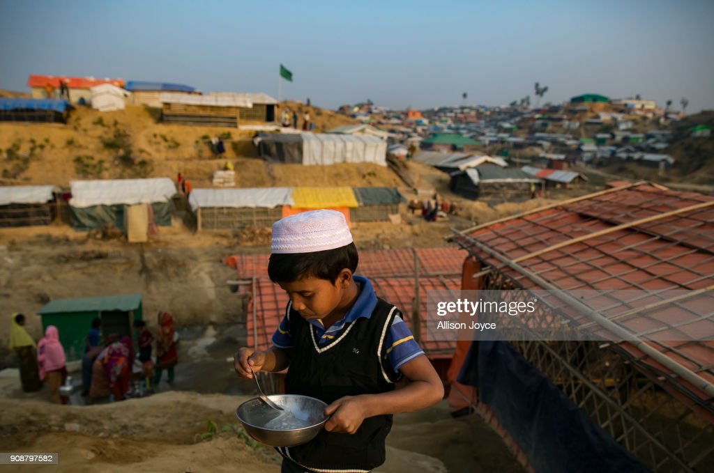 COX'S BAZAR, BANGLADESH - JANUARY 17: A child eats on January 17, 2018 in Cox's Bazar, Bangladesh. In the refugee settlement of Balukhali, over 116 widows and orphans have found shelter within a dense settlement of 50 red tents where no men or boys over the age of 10 years old are allowed. More than 655,000 Muslim Rohingya have crossed the border into Bangladesh since August last year, when they fled Rakhine state after the Myanmar military launched a brutal crackdown which was described by the United Nations as 'ethnic cleansing'. Women and girls reportedly make about 51 percent of the distressed and traumatized Rohingya population in the refugee camps and face a high risk of being victims of human trafficking and sexual abuse, while adolescent girls aged between 13 and 20 risk getting involved in forced marriages. Many of the Rohingya women travelled alone after their husbands had been killed or taken away during the attacks on Rohingya villages as many continue to fear returning home due to the lack of security guarantees.