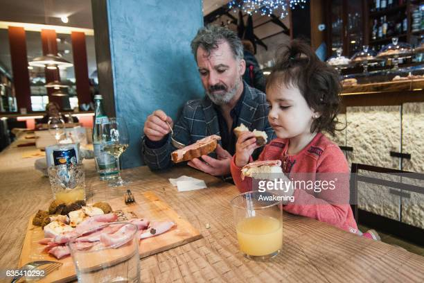 Child eats with her parents for lunch at a table in the Antonio Ferrari restaurant on February 15, 2017 in Padova, Italy. The restaurant offers a 5%...