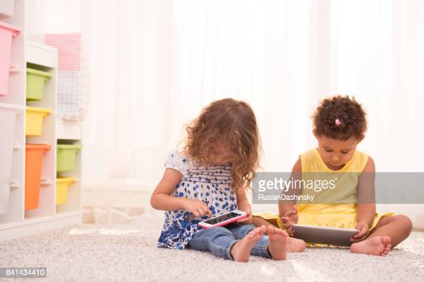 Child electronic gadget addiction. Little girls using communication devices and missing life communication.