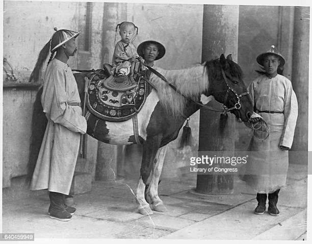 Child emperor Kuanghsu sits atop a horse while royal attendants look after him