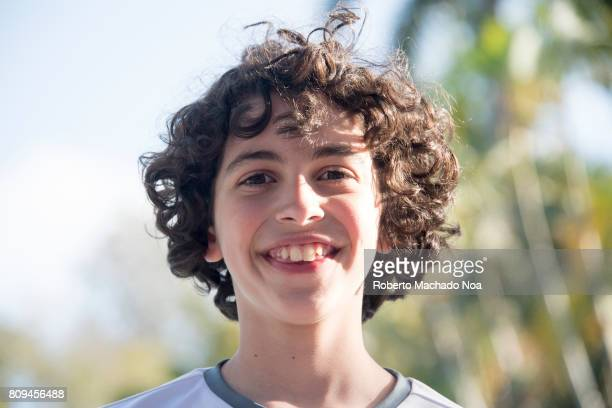 Child enjoying Cuban nature portrait Curly haired and buck toothed smiling child boy against a blurred background