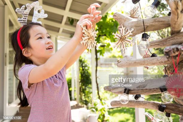Child enjoying decorating Christmas tree with antler headband