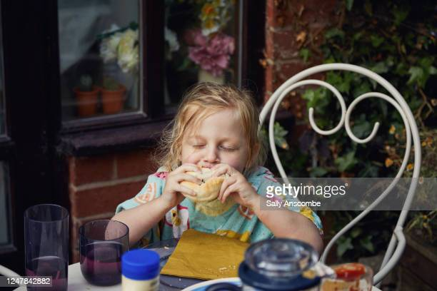 child enjoying eating a burger at a barbecue - burger stock pictures, royalty-free photos & images