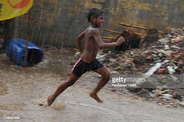 Child enjoying pre-monsoon rain on June 16, 2013 in Noida, India. The national capital has been witnessing pre-monsoon showers, recording 6.1 mm of...
