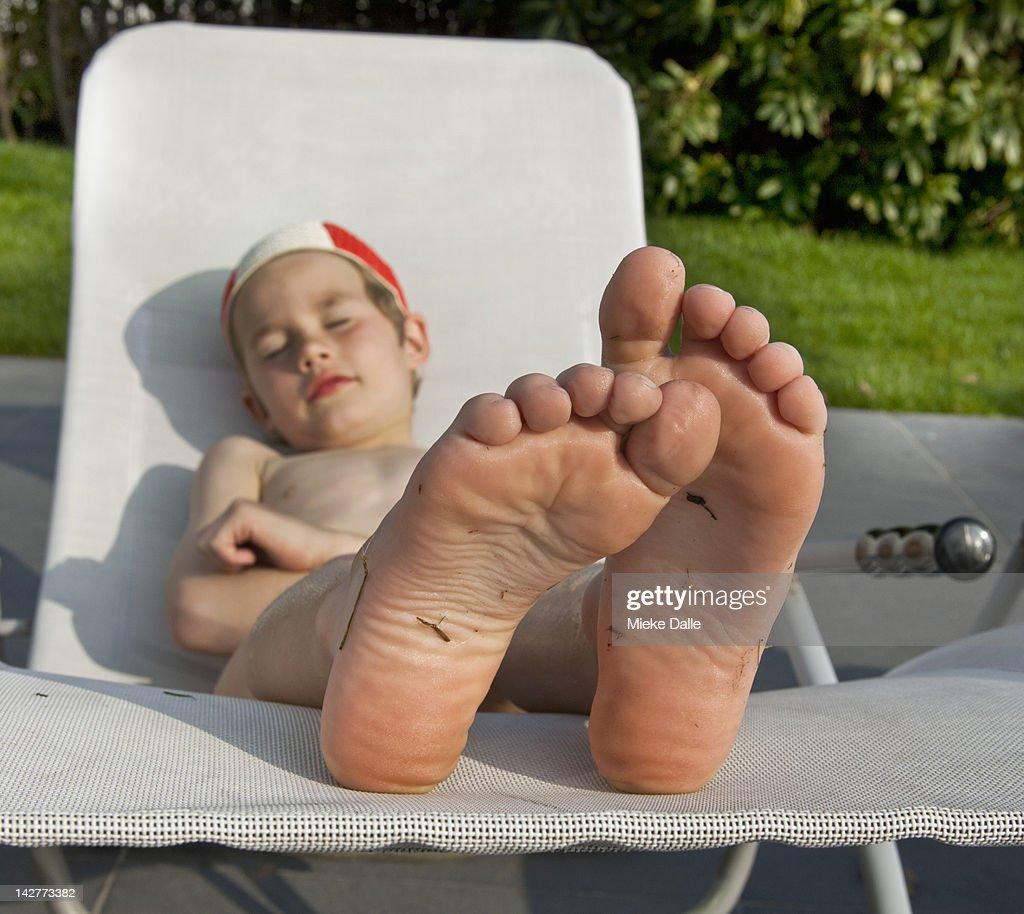 Child enjoying the sun on a lounger : Stock Photo