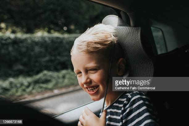 child enjoying the wind blowing through his hair in the back seat of a car - europe stock pictures, royalty-free photos & images