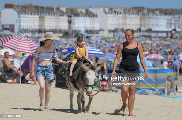 Child enjoys a donkey ride on July 18, 2021 in Weymouth, England. A heat-health warning has been issued for England this weekend, with temperatures...