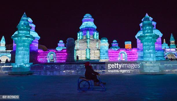 A child enjoys ice track cycling as she rides past an illuminated ice castle during the 33rd Harbin International Ice and Snow Festival at Harbin Ice...
