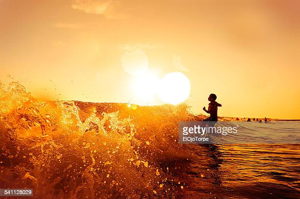 Child entering the sea, breaking wave, sunset