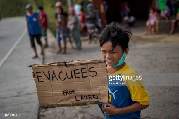 A child evacuee holds up a sign as he waits for relief goods at the side of a highway on January 20 2020 in Tagaytay city Cavite province Philippines...