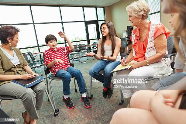 Child explaining something to group of adults and children