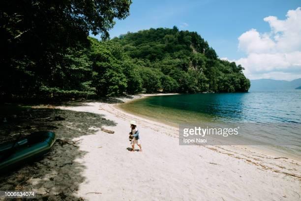 Child exploring secluded lake beach, Lake Chuzenji, Nikko, Japan