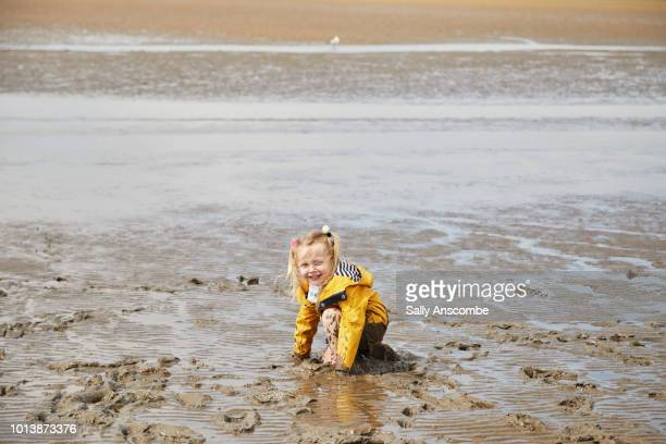 Child falling over in the muddy sand