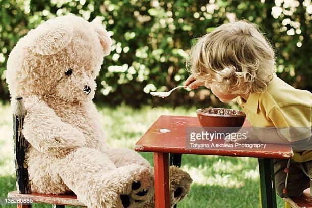 child feeding his teddy bear - alimentar fotografías e imágenes de stock