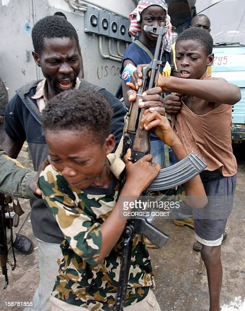 A child fighter of the LURD rebel force is molested by other fighters in the Freeport suburb in Monrovia after he was caught looting a goods depot...