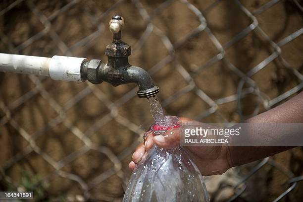 A child fills a bottle with water from a public tap in the 8th Commune in Medellin Antioquia department Colombia on March 22 2013 The commune...