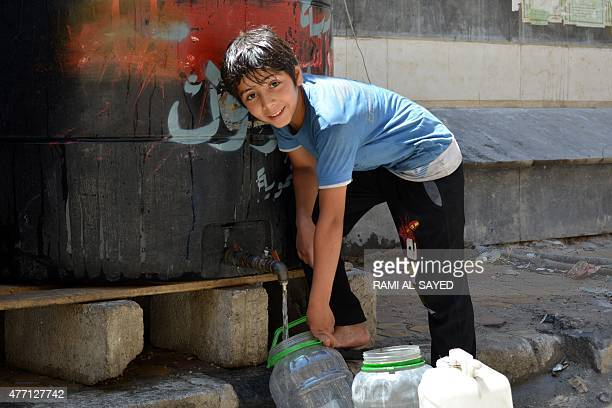 A child fills a container with water on June 14 2015 in Yarmuk Palestinian refugee camp south of the Syrian capital Damascus Before the Syria...
