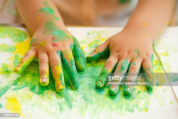 Child finger painting, cropped
