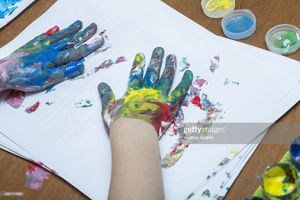A child finger painting on paper : Stock Photo