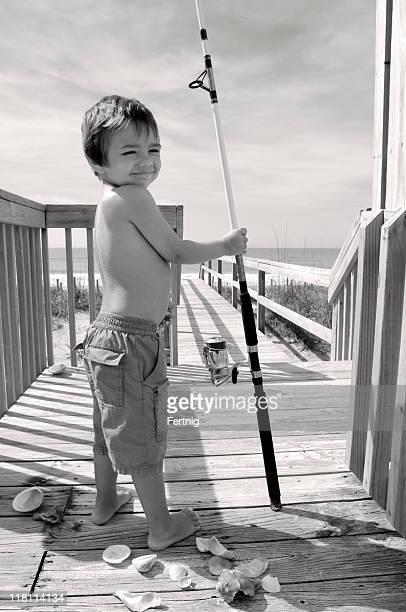 Child fisherman heading to the seaside
