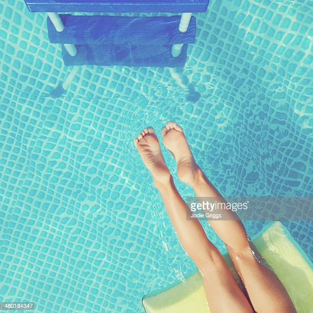 Child floating in swimming pool in warm summer sun