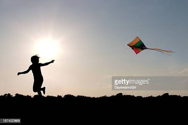 Child flying a multicolored kite outside