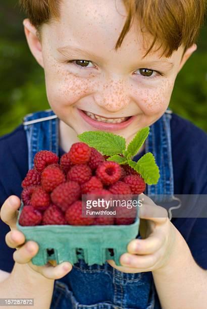 Enfant de Jardinier avec des fruits rouges de framboise, garçon tenant panier de fruits
