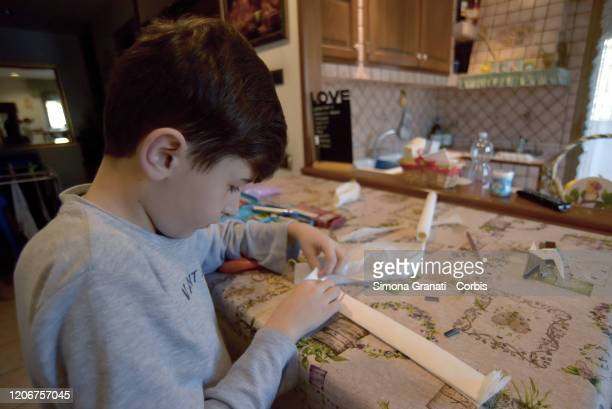 A child forced to stay at home for the measures against the Coronavirus builds protective masks now unobtainable DIY with baking paper on March 12...