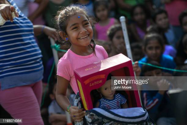 A child from El Salvador receives a donated doll following class at The Sidewalk School held at a Remain in Mexico camp for asylum seekers on...