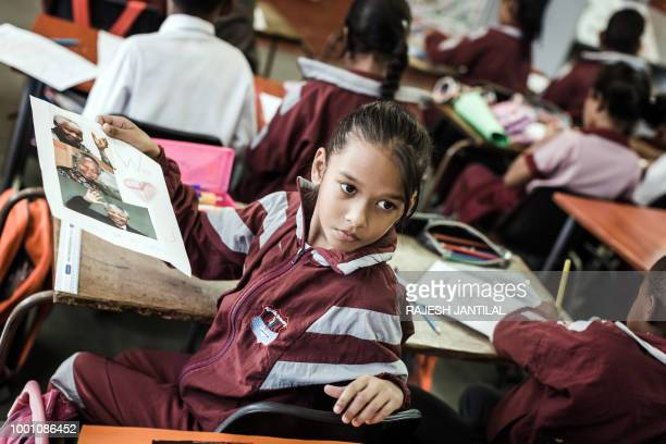 A child from Northlen Primary school colour in posters to commemorate the life of former South African President Nelson Mandela in Durban on July 18...