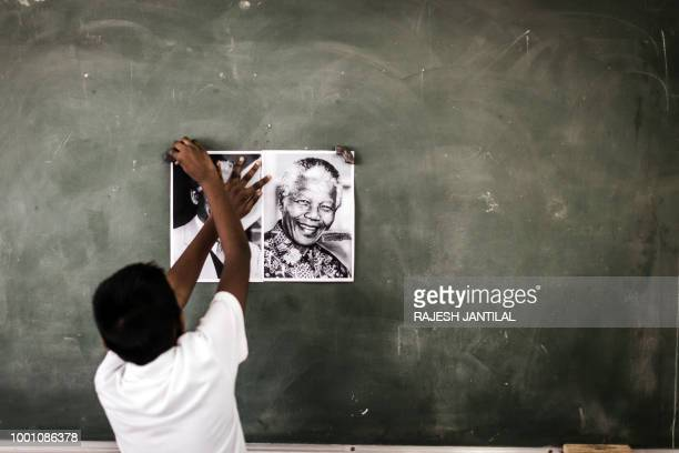 TOPSHOT A child from Northlen Primary school sticks a poster of former South African President Nelson Mandela on the chalkboard in Durban on July 18...