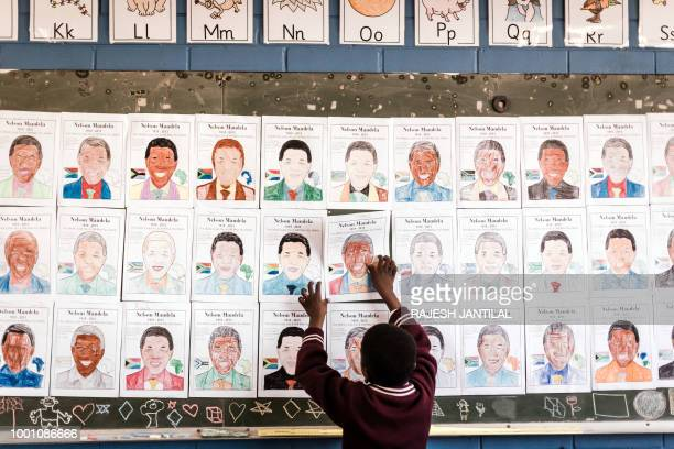 A child from Northlen Primary school sticks a poster on the chalkboard of former South African President Nelson Mandela in Durban on July 18 2018...