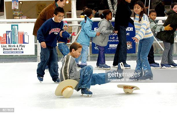 A child from Para Los Aninons loses his footing while ice skating at Pershing Square outdoor skating rink during the Disney On Ice Christmas tree...
