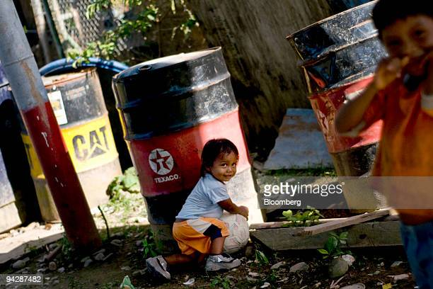 A child from the Huaorani tribe also known as the Waos who are native Amerindians from the Amazonian Region of Ecuador plays near a discarded Texaco...