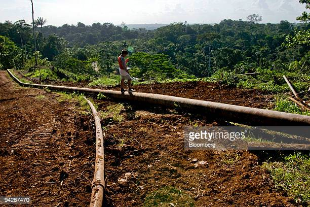 A child from the Huaorani tribe who are native Amerindians from the Amazonian Region of Ecuador stands on an oil pipeline belonging to China's...