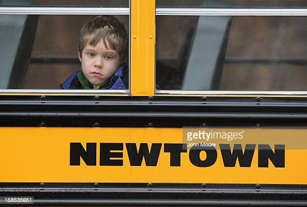 Child gazes from a school bus as it passes by the St. Rose of Lima Catholic church while mourners gathered for a funeral service for shooting victim...