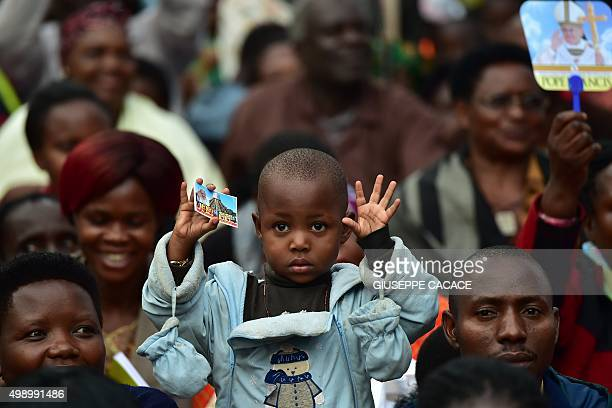 A child gestures as people wait for the arrival of Pope Francis for an open mass at Namugongo Martyrs' Shrine in Namugongo Uganda November 28 2015...