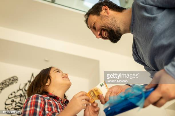 child getting eid money from father - eid al adha stock pictures, royalty-free photos & images