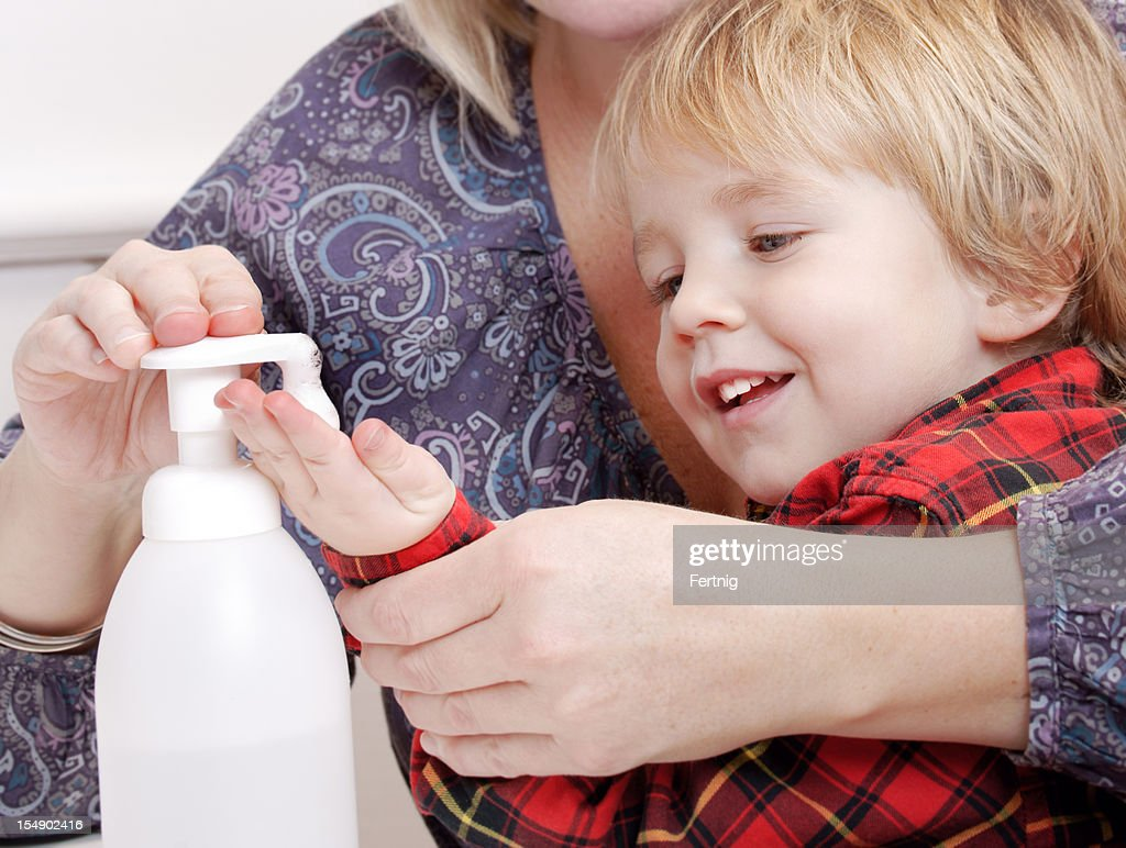 Child getting help applying antiseptic hand sanitizer : Stock Photo