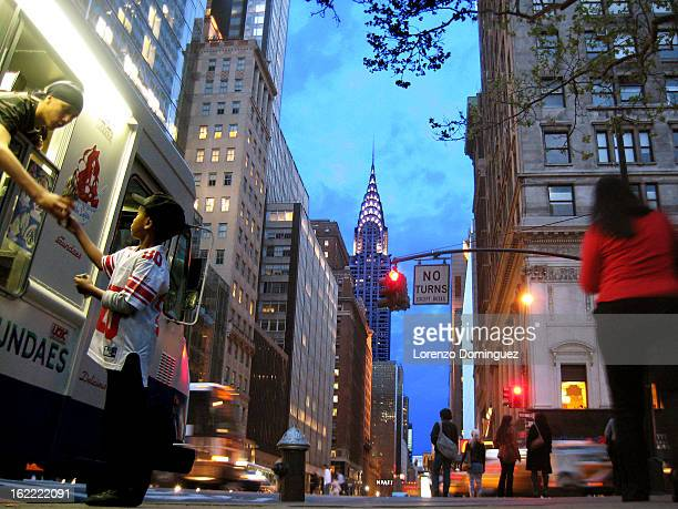 CONTENT] Child getting ice cream in New York City on 42nd Street with Chrysler Building in the background