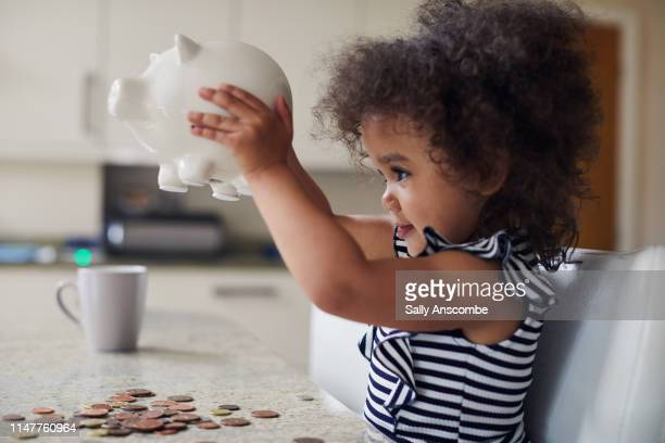 child getting money out of her piggy bank - coin photos stock pictures, royalty-free photos & images